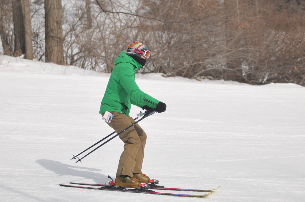 Picture of an adult wearing a green ski coat and beige snow pants, racing in an adult league program at Mt. Holly.