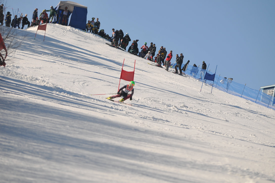 Picture of the Mt. Holly Race Hill. The hill is large and there are many people at the top which include ski racers and their coaches. There is a race shack, or small building at the top where racers stand, waiting to get the go ahead to begin racing down the hill. The slope is steep and snowy and there is one single ski racer racing down the hill past a red flag. They appear to be wearing a black racing suit and a green helmet. The sky is blue and it is a sunny day.