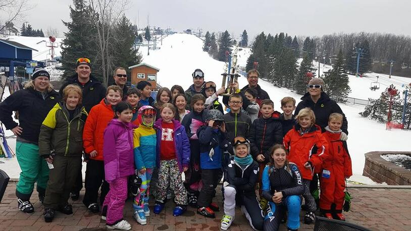 Picture of a large group of people who are involved in Thunderbolt Racing at Mt. Holly. The majority of the people are children and teens who are dressed in bright winter coats and snowpants. There are also adults who are coaches and people who help support the program. They are standing outside at Mt. Holly on a brick patio and there is snow and pine trees behind them.