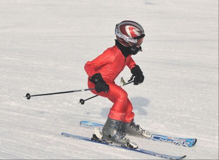 Picture of a child in ski racing gear, skiing down a snowy slope.