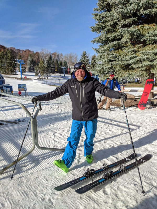Picture of Kurt Payne standing in his skis outside of the ski school doors. There is snow on the ground and in the trees and the sky is blue. He is wearing blue ski clothing and he is smiling, grateful for such a beautiful day.