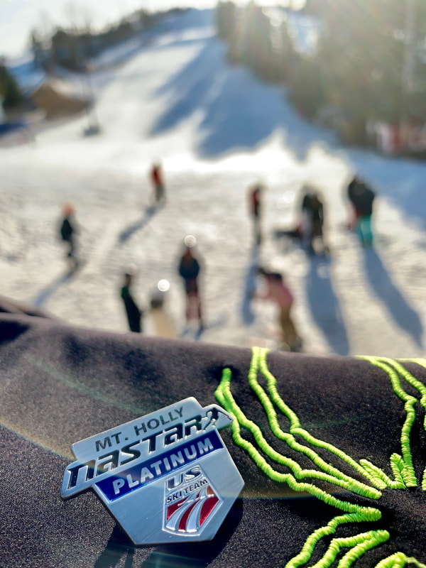Picture of a NASTAR racing medal sitting on a ledge with the ski hill in the background. NASTAR stands for National Standard Race and is the largest public grassroots ski racing program in the world. Mt. Holly hosts NASTAR races on the race hill.