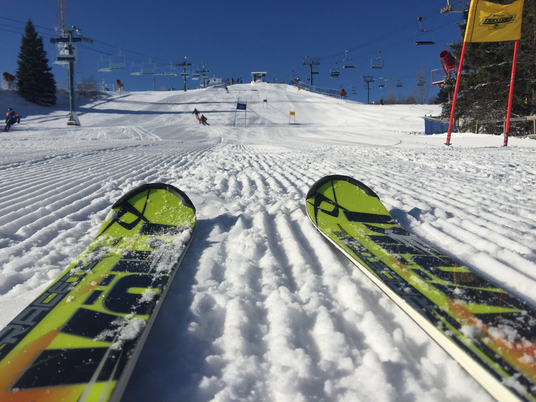 Picture of two skis on the freshly groomed snow, a race hill ahead. The chairlift is off to the side, bringing skiers to the top of the hill. The sky is blue and it is a bright cheerful day.