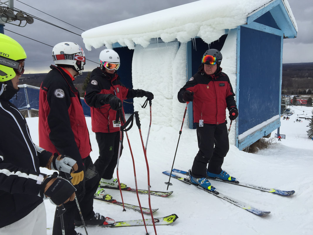 Picture of Mt. Holly ski instructors in red and black coats, standing at the top of the ski racing hill near a small structure that serves as a building where the ski racers start their timed runs on the race course. They are standing in their skis on the snow and talking.