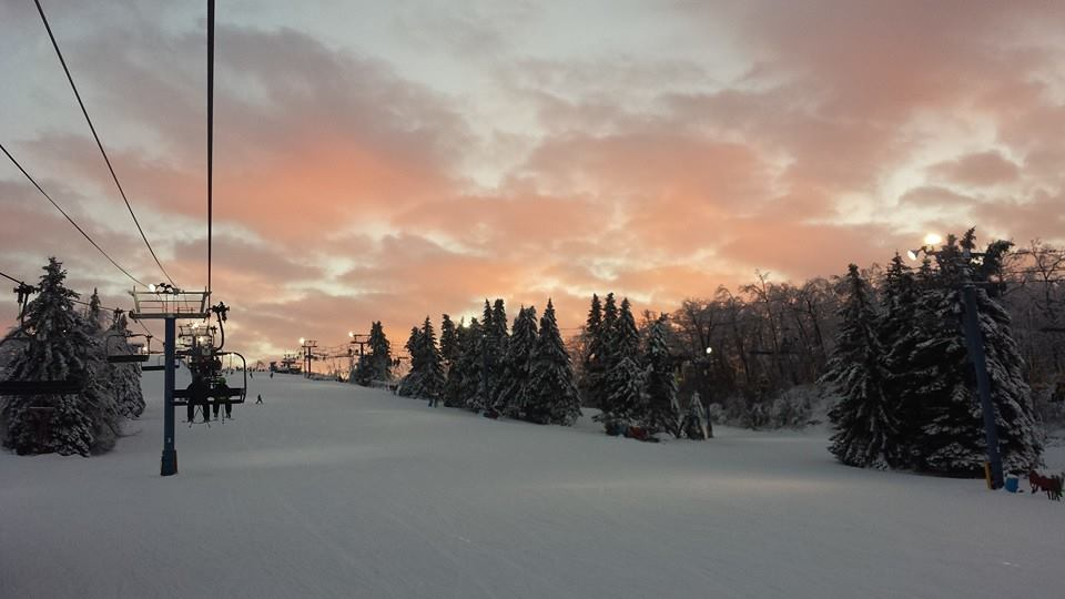 A beautiful picture of Mt. Holly Ski and Snowboard resort. This picture is showing one of the ski hills from the bottom. There is a chairlift carrying people to the top of the hill on the left and to the right are pine trees covered in snow. The sky is filled with beautiful clouds that are soft purple and pink colors. The ski hill is snowy and it looks like a lovely and inviting place to go skiing.