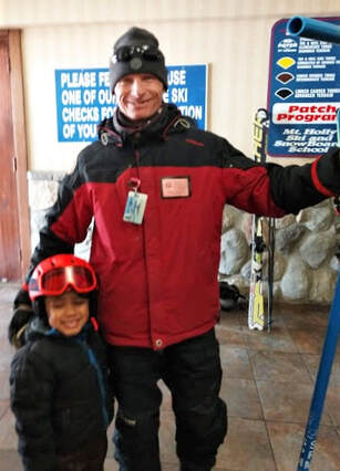 Picture of a Mt. Holly Ski Instructor wearing a red and black coat standing next to a young student who is wearing a black coat and a red helmet. They are standing indoors near the ski school and are about to head outside to the snowy slopes for a lesson that will provide fun, safety, and increased confidence for the student.